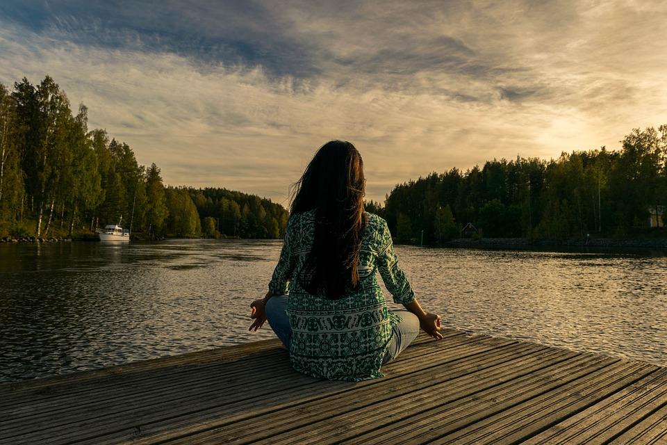 Mediterende kvinde ved vand